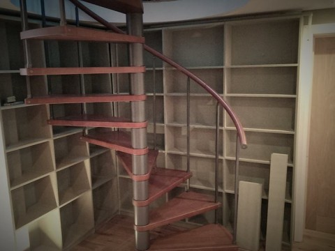 Photo of bookcase behind spiral staircase